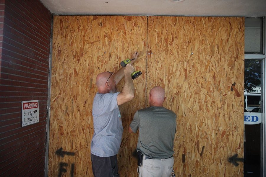 MYRTLE BEACH, SC - SEPTEMBER 11:  Jay Schwartz (L) and Michael Schwartz secure plywood over the windows of their business ahead of the arrival of Hurricane Florence on September 11, 2018 in Myrtle Beach, South Carolina. Florence is expected to make landfall by late Thursday to near Category 5 strength along the Virginia, North Carolina and South Carolina coastline.  (Photo by Joe Raedle/Getty Images)