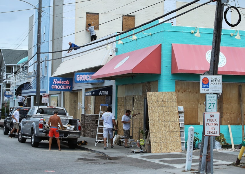 WRIGHTVILLE BEACH, NC - SEPTEMBER 11: Workers board up shops while preparing for the arrival of Hurricane Florence on September 11, 2018 in Wrightsville Beach, United States. Hurricane Florence is expected on Friday possibly as a category 4 storm along the Virginia, North Carolina and South Carolina coastline.  (Photo by Mark Wilson/Getty Images)