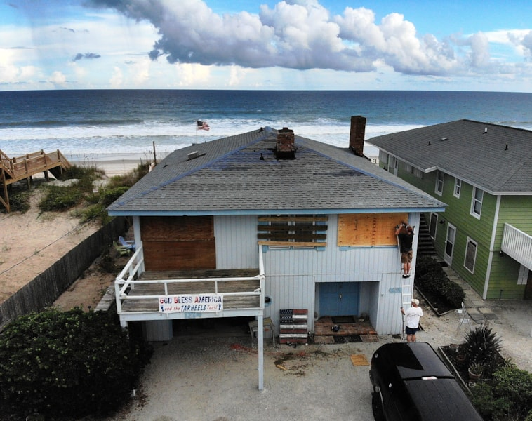 SURF CITY, NC- SEPTEMBER 11: John Edwards holds a ladder for his son William Edwards while he attaches a sheet of plywood over a window of their family's beach cottage while preparing for the arrival of Hurricane Florence on September 11, 2018 in Surf City, North Carolina. Hurricane Florence is expected on Friday possibly as a category 4 storm along the Virginia, North Carolina and South Carolina coastline.  (Photo by Mark Wilson/Getty Images)