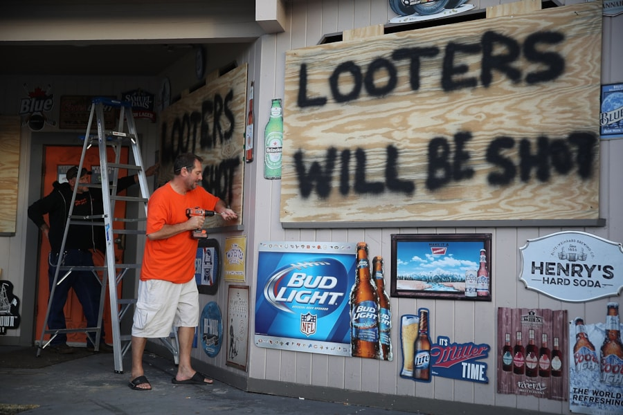 MYRTLE BEACH, SC - SEPTEMBER 12:  Doug Lewis (L) and Chris Williams use plywood with the words 'Looters will be shot' to cover the windows of Knuckleheads bar as they try to protect the business ahead of the arrival of Hurricane Florence on September 12, 2018 in Myrtle Beach, United States. Hurricane Florence is expected on Friday possibly as a category 4 storm along the Virginia, North Carolina and South Carolina coastline.  (Photo by Joe Raedle/Getty Images)